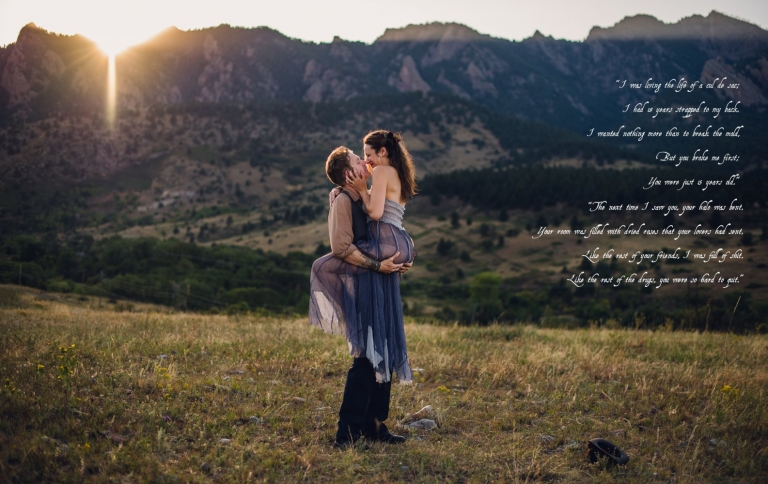 couple embraces at sunset in front of boulder mountains