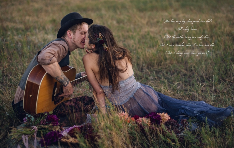 man holding guitar kissing woman wearing a blue free people dress during couples picnic