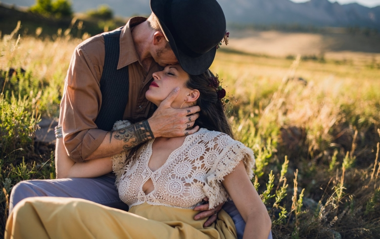 man kissing a woman in a yellow dress surrounded by golden grass in boulder