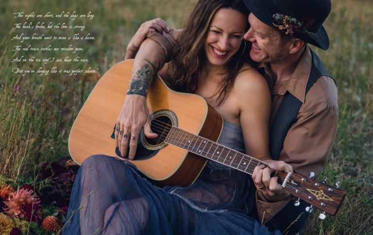 bohemian couple snuggling while holding a guitar