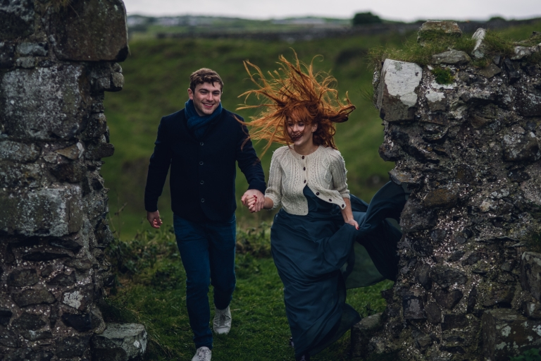 young couple walking through rocky remains of a castle in northern ireland as the woman's red hair blows wildly in the wind