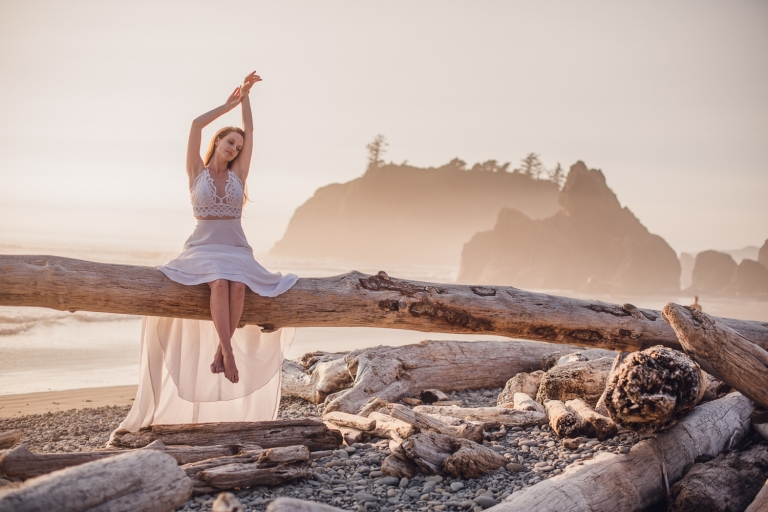 red head bride sitting on a driftwood tree stretching towards the sky at sunset on ruby beach